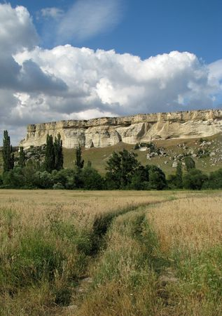 Lane to the cliff. Summer landscape. Scenic cliff in the steppe. Cloud-drift. Stock Photo