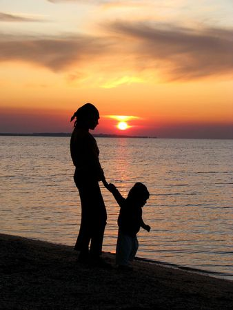Walk in the evening.  Sister and brother are walking in the sundown. Children on the seaside in the sunset.