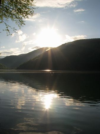 Sunny morning on the mountainous lake. Sun and its reflection in the water.