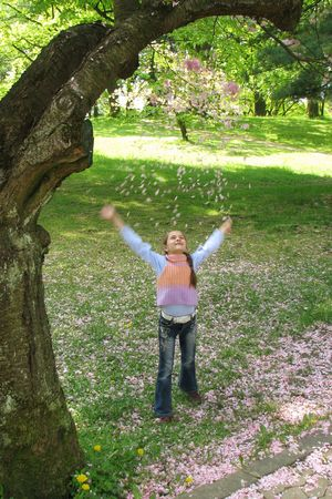 Spring happy.  Girl throws up pink petal of cherry. Spring fun.