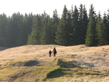 Family hike. Mother and daughter walking on the autumnal grassland. Stock Photo