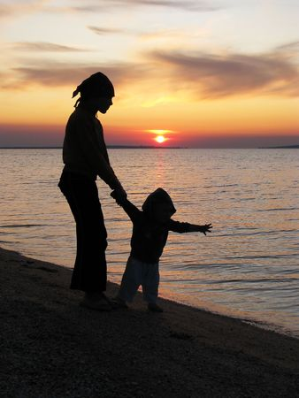 Evening walk.  Sister and brother are walking in the sundown. Children on the seaside in the sunset.    Stock Photo