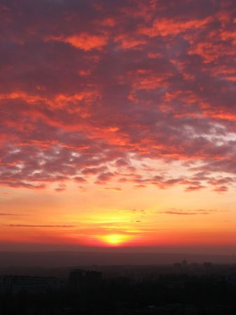 Dawn. Early morning. Sunrise above the city. Red cloud-drift.