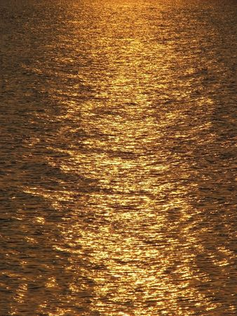 Sunny reflection. Reflection of the sundown in the sea. Solar patches of light on water. Solar path.