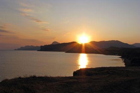 Sundown.  Sunset on the South Coast of Crimea. Bay of Sudak in the evening.  Stock Photo