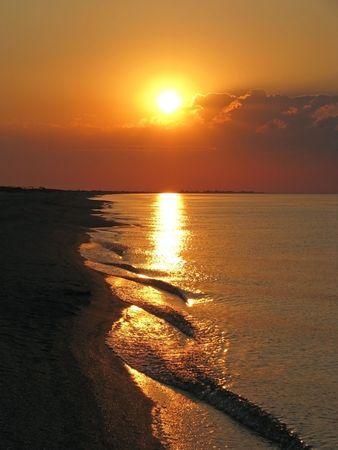 Evening on the seaside. The orange sea sunset on the seashore. Sunny evening on the seaboard.