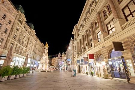 Pestsaule between illuminated buildings at night at Graben street in Vienna, Austria Foto de archivo