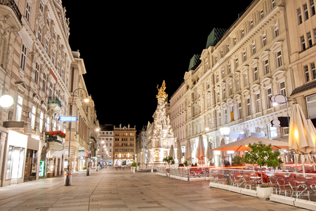 Pestsaule between illuminated buildings at night at Graben street in Vienna, Austria Banco de Imagens