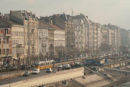 Urban scene - boulevard and houses on the Danube in the Hungarian capital Budapest with cars and tram on a foggy day
