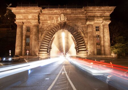 Long exposure at night. Fast cars pass through a tunnel in Budapest, the capital of Hungary, Eastern Europe, a tunnel right next to the banks of the Danube and the Chain Bridge in Buda Banco de Imagens - 133462681