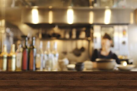 Top wood table blur chef cooking in bar restaurant background.For create product display or design key visual layout. Blur bartender serving coffee to customer.