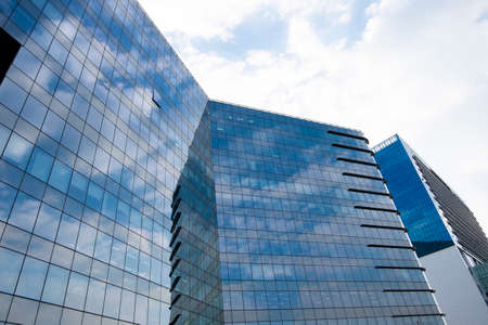 Highrise glass building with sky and clouds reflection. geometric shapes and buildings Banque d'images