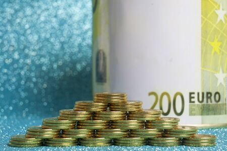 Pyramid of stacks of gold coins on a blue background and the sign of the euro zone.