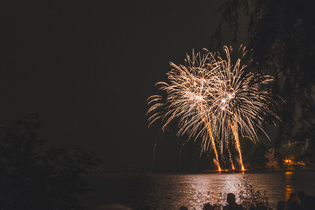 Fireworks explode from the margin of a river