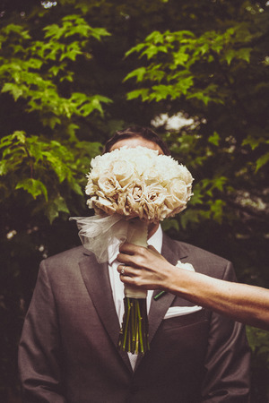 Bride hides groom with her flower bouquet Reklamní fotografie