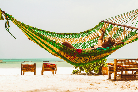 Woman relaxing in a hammock in a tropical beach