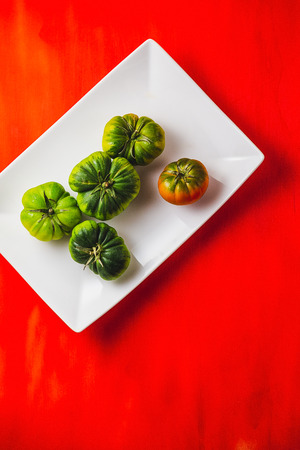 Plate of green tomatoes in a red table
