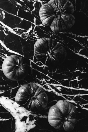 Black and white tomatoes in a marble background Reklamní fotografie