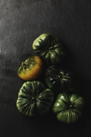 Green tomatoes in a graffiti background in a moody light