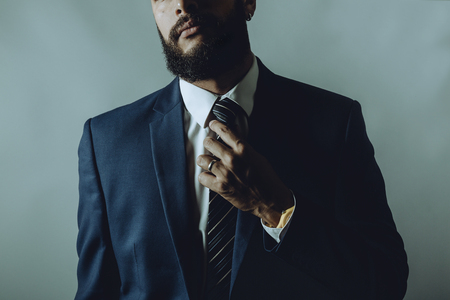 Beard man in a suit fixes tie