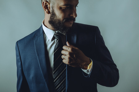 Beard man in a suit smiles while fixes tie