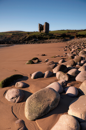 irish history: castle ruins at minard beach with rocks in foreground