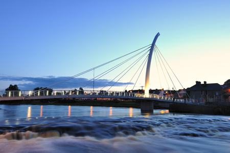 resemble: River Moy at Ballina, Co.Mayo, Ireland, with pedestrian bridge, part of which is  shaped to resemble fishing rod