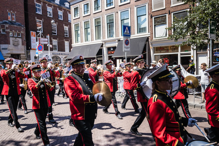 The Haaglanden Drum Fanfare Orchestra in red uniform performing and marching at the parade on the 2018 Veterans Day in The Hague