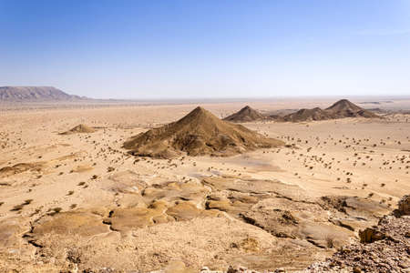 A desert landscape viewed from the Natural Arch of Riyadh. A plain surrounded by the mountain ridge - a Martian-like landscape.