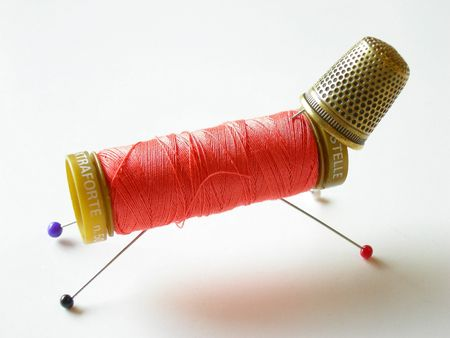 threaded: Thread, thimble and needle on white background.