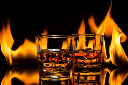 glass of whiskey with ice on a background of a burning flame