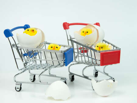 Small chickens in an eggshell on a small shopping cart. Easter.