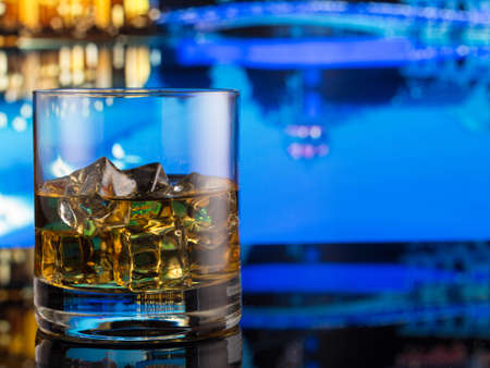whiskey in a glass with ice on a background of a night pool Reklamní fotografie