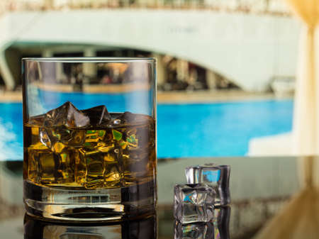 whiskey in a glass with ice on the background of the pool
