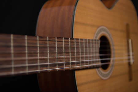 Acoustic guitar lying on a black background. From different angles.