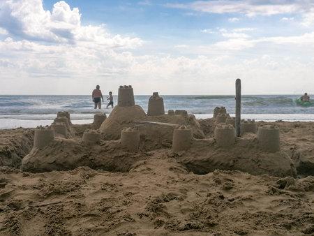 A sandcastle on a sandy beach, set against a bright blue summer sky.