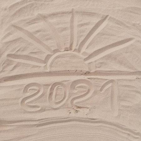 2021 inscription on the sand of the beach. Summer beach holidays in 2021.