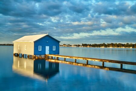 Rustic blue house with a wooden bridge in the middle of the water
