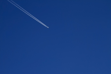 Airplane in bright blue sky photo