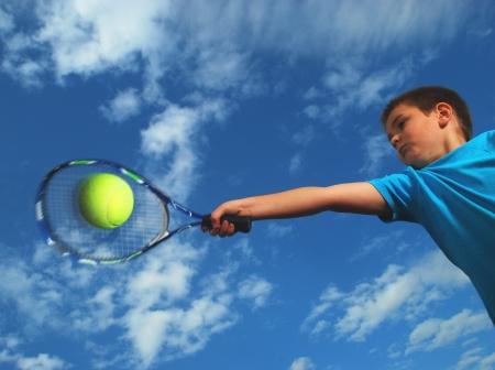 oefenen: tennis. Een kleine jongen het slaan van een forehand geschoten met racket Stockfoto