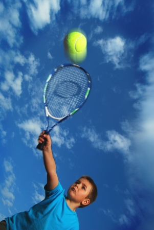Tennis serve from little boy photo