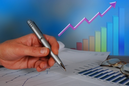A hand of business person with pen pointing towards accounting graphs and tables of a successful business Banque d'images