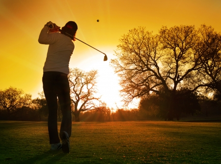 Golfer Golf zonsondergang speelt slag in de ondergaande zon Stockfoto