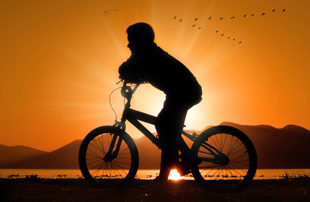 little boy on bicycle silhouette at sunset