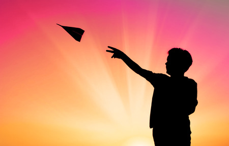 silhouette of boy throwing paper plane Stock Photo