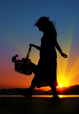 Little girl with flowers playing outside, silhouette
