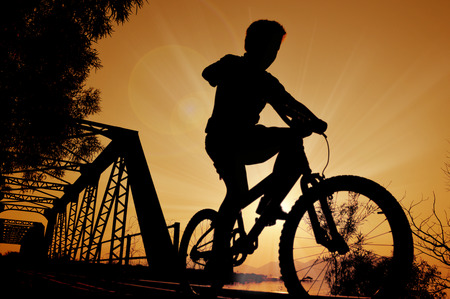 little boy riding bicycle silhouette Stock Photo