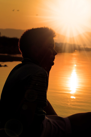 little boy silhouette at lake, sunset Banque d'images