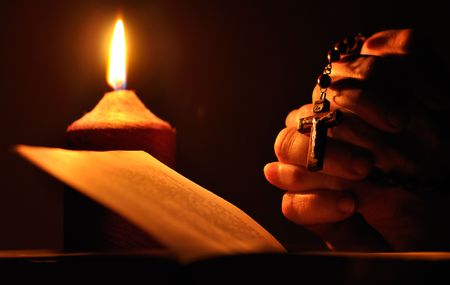 Still life with candle, prayer book and prayer hands Stock Photo
