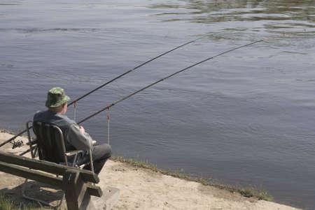hombre pescando: Pesca del hombre en el r�o. Foto de archivo